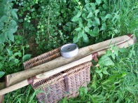 Picture of vintage wicker creel, rod bag and vintage fishing bait tin.