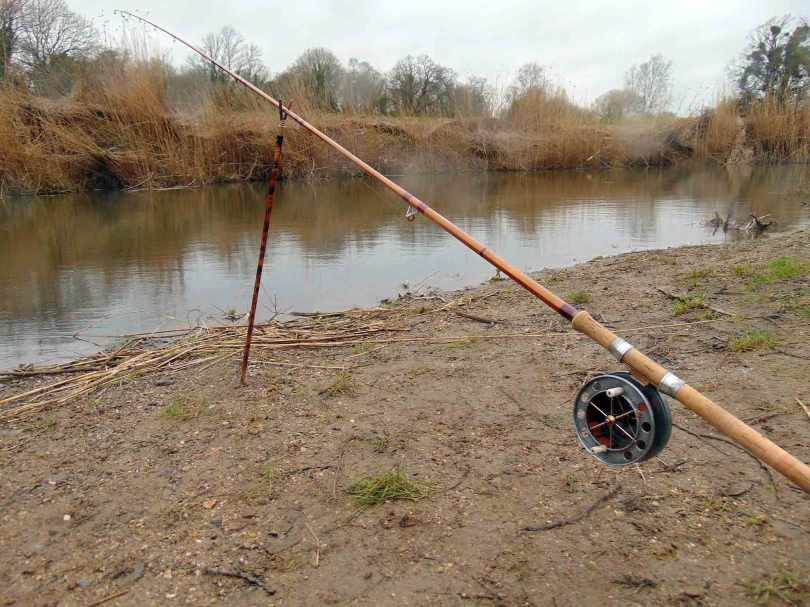 Picture of a Fred J. Taylor rod and Allcocks Aerial fishing reel sitting in a rod rest at the edge of a river.