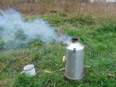 Picture of a boiling Kelly Kettle with mug ready for the hot water
